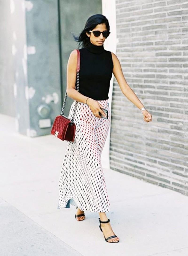 7b4f7b7d7594 Πουά μακριά φούστα συνδυασμένη με αμάνικο ζιβάγκο και μαύρα πέδιλα. Key  piece  H κόκκινη τσάντα Chanel με το λουράκι αλυσίδα.